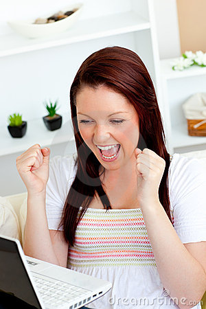 Mujer emocionada con los brazos para arriba delante de su computadora portátil
