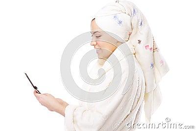 Mujer en albornoz con el sideview del teléfono