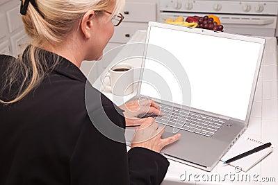 Mujer en cocina usando la computadora portátil con la pantalla en blanco