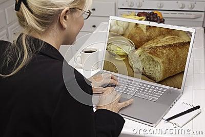 Mujer en cocina usando la computadora portátil - alimento y recetas
