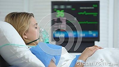Mujer en coma, frecuencia cardíaca en el monitor de ecg, unidad hospitalaria de cuidados intensivos almacen de metraje de vídeo