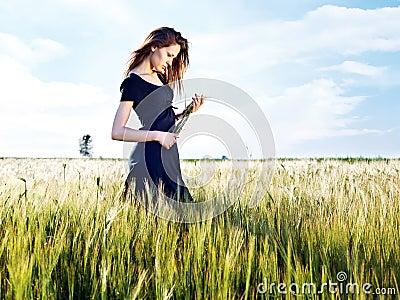 Mujer en el campo de trigo en día asoleado