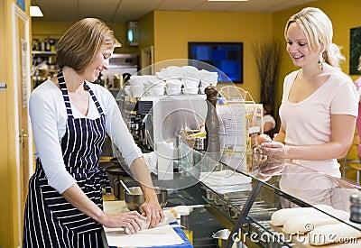 Mujer en el contador en cliente de la porción del restaurante
