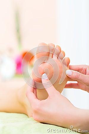 Mujer en el salón del clavo que recibe masaje del pie