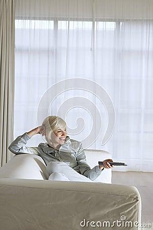 Mujer en el sofá que ve la TV