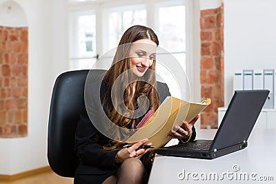 Mujer en la oficina que se sienta en el ordenador