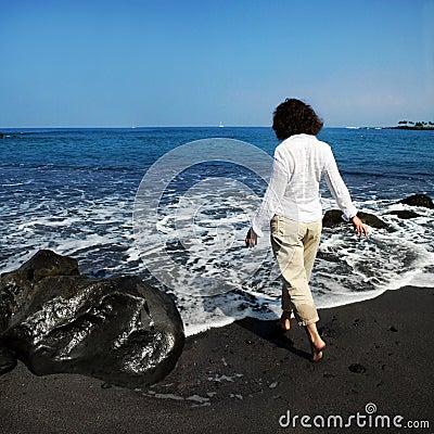 Mujer en la playa negra de la arena