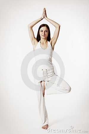 Mujer en la postura de la yoga del árbol (Vrikshasana)