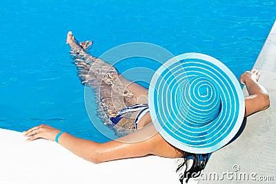 Mujer en sombrero azul en la piscina