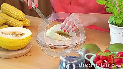 Mujer en una blusa rosada que taja un melón amarillo jugoso metrajes