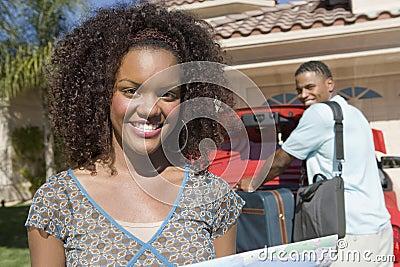 Mujer feliz con el hombre que mantiene el equipaje coche