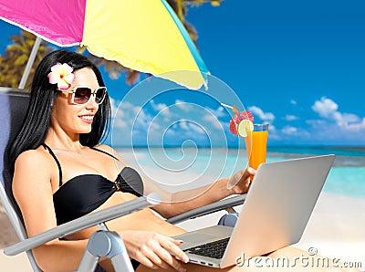 Mujer feliz en la playa con una computadora portátil
