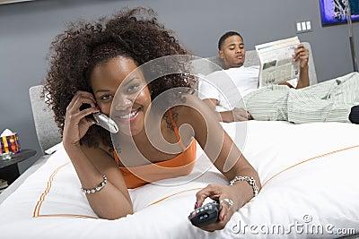 Mujer feliz en llamada mientras que ve la TV en dormitorio
