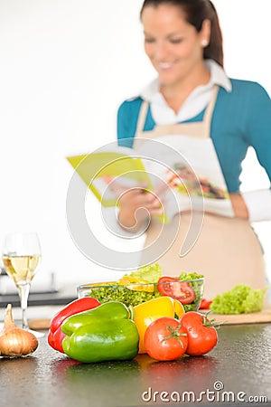 Mujer feliz que prepara las verduras de la receta que cocinan la cocina