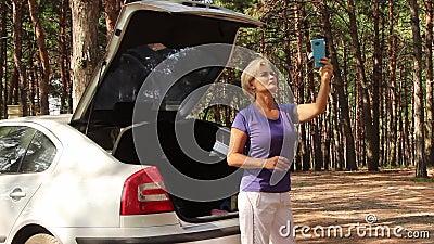 Mujer hermosa en el bosque trata de atrapar una señal en un teléfono celular almacen de video