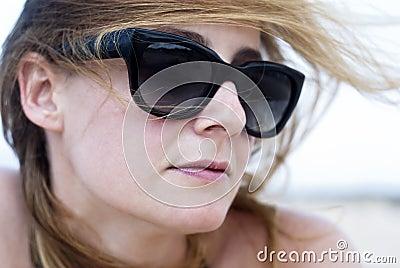 Mujer hermosa en gafas de sol en una playa
