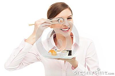 Mujer hermosa que come el sushi