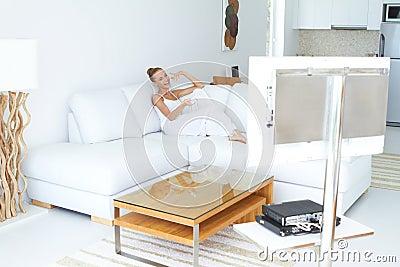 Mujer hermosa que ve la TV en de interior casero