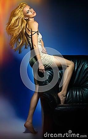 Mujer joven atractiva que presenta en el sofá