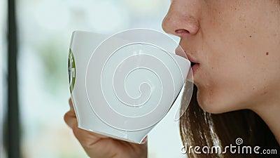Mujer joven bebe café matutino con galleta metrajes