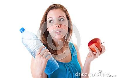 Mujer joven con la botella de agua y de manzana