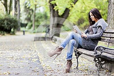 Mujer joven con la tablilla en el banco