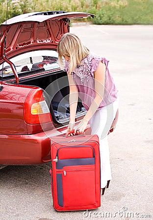 Mujer joven con una maleta roja en el coche