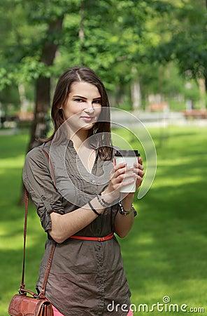 Mujer joven con una taza de café en parque