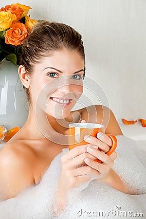 Mujer joven de la belleza en el baño que bebe té herbario