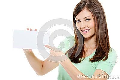 Mujer joven de la belleza que señala en la tarjeta en blanco