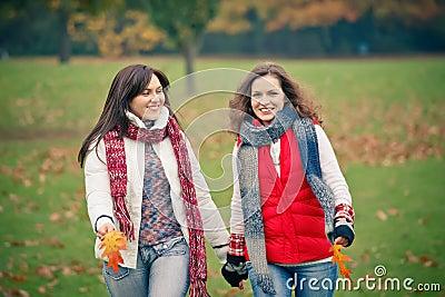 Mujer joven dos que recorre en parque del otoño