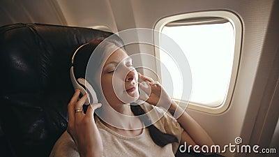 Mujer joven en auriculares inalámbricos que escucha la música y que sonríe durante mosca en aeroplano metrajes