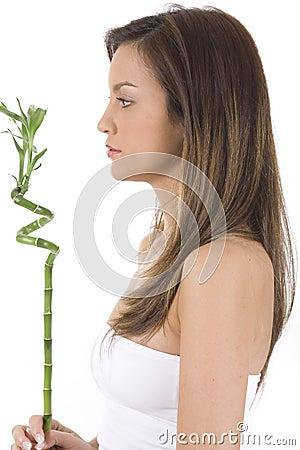 Mujer joven en el bambú blanco del verde de la explotación agrícola.