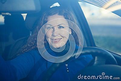 Mujer joven en el coche que se prepara a la conducción