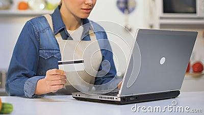 Mujer joven en el delantal que inserta el número de tarjeta de crédito en el ordenador portátil, tienda del producto en línea almacen de metraje de vídeo