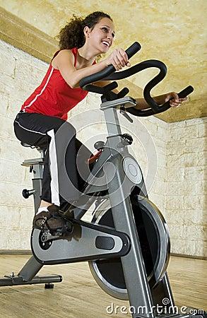 Mujer joven en la bici de ejercicio