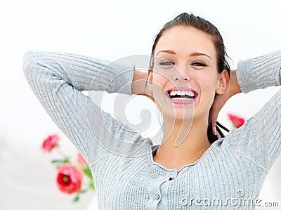 Mujer joven feliz con las manos detrás del cuello