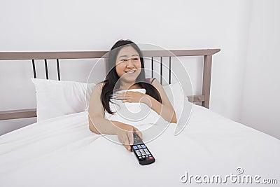 Mujer joven feliz que ve la TV en cama