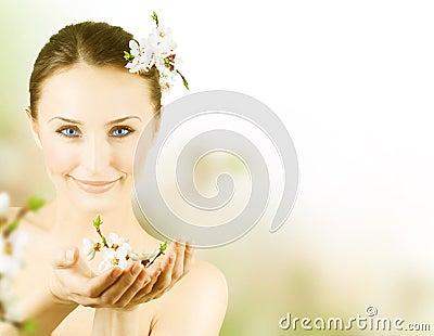 Mujer joven hermosa con el flor del resorte