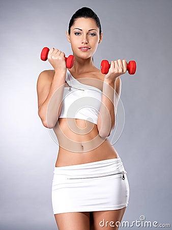 Mujer joven hermosa con pesas de gimnasia