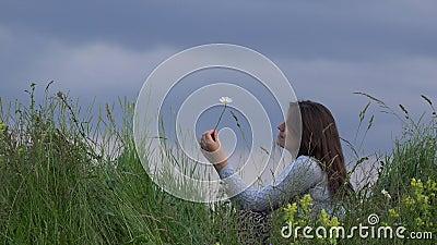 Mujer joven hermosa que juega y que huele una margarita, cielo azul del cierre del pico de la colina metrajes