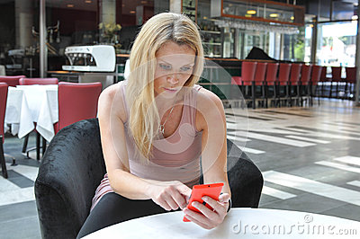Mujer joven hermosa que usa un teléfono elegante
