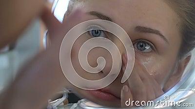 Mujer joven que aplica la crema del ojo, cosmético de la anti-edad, cuidado de piel, rejuvenecimiento metrajes