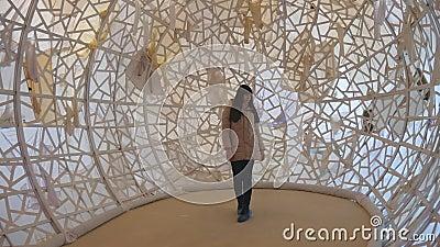 Mujer joven que camina dentro de objeto del arte contemporáneo en el museo Muchacha que examina arte moderno almacen de metraje de vídeo