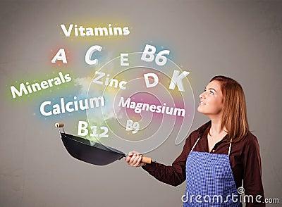 Mujer joven que cocina las vitaminas y los minerales