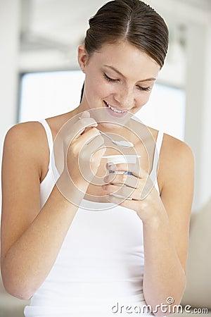 Mujer joven que come el yogur