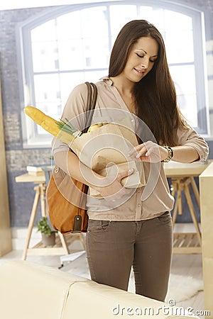 Mujer joven que comprueba tiempo como conseguir el hogar