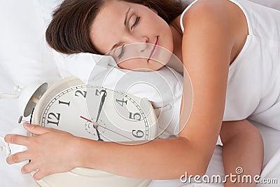 Mujer joven que duerme en cama con el reloj de alarma