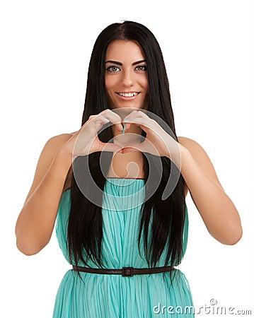Mujer joven que forma dimensión de una variable del corazón con las manos