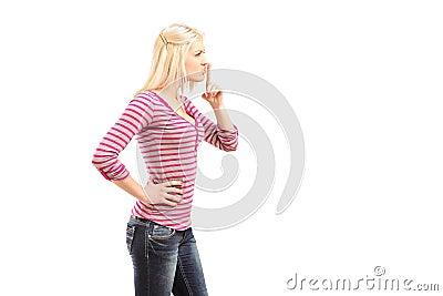 Mujer joven que gesticula silencio con el dedo sobre boca